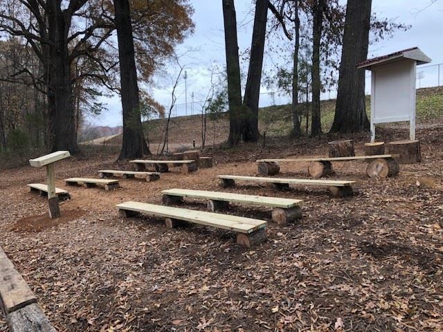 rows or wooden benches going up a hill, serving as an outdoor classroom.  There is a podium in the front and a sign with a roof in the back.